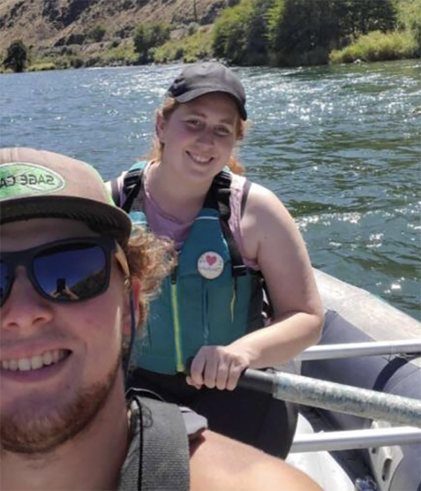 Amy and a guy in a raft with lifejackets and hats on smiling on the Deschutes river