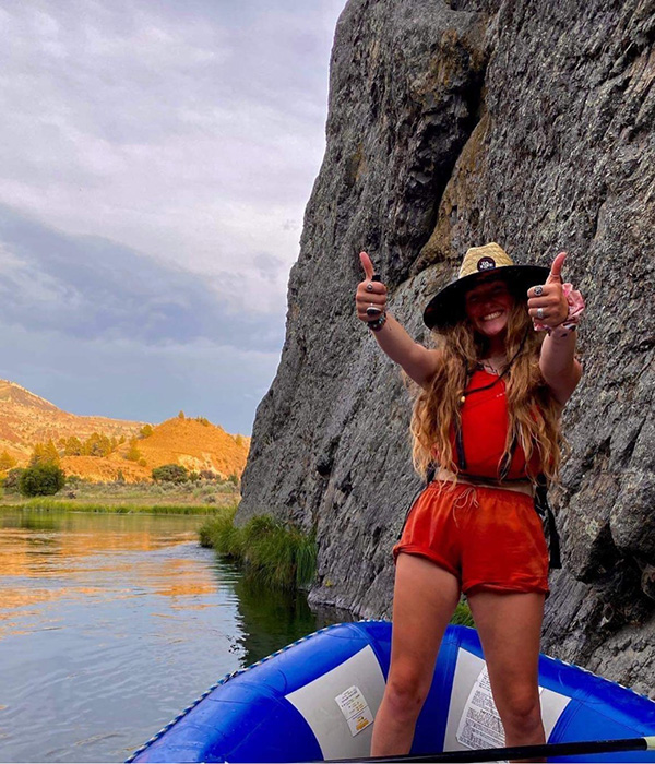 Kailyn in her water gear giving thumbs up from her raft on a calm part of the deschutes river in Maupin, Oregon